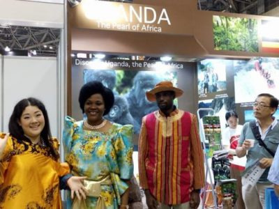 A Japanese lady smiles in a gomesi at the expo